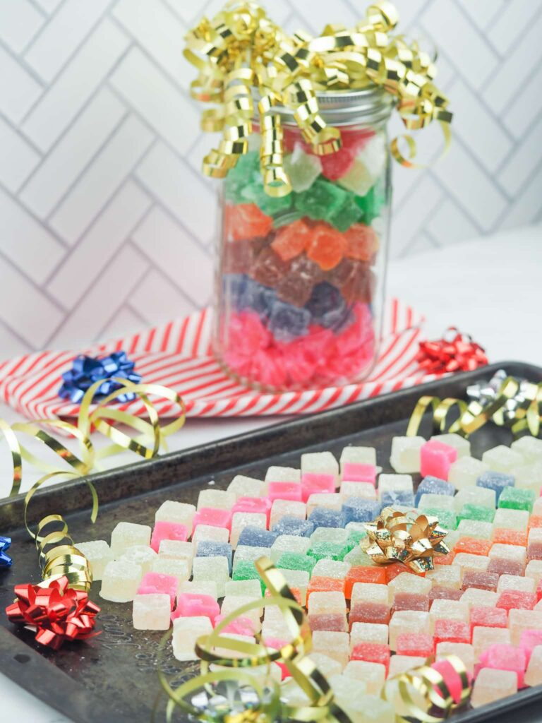 hard tack candy arranged on baking sheet with ribbons and jar of candy in background