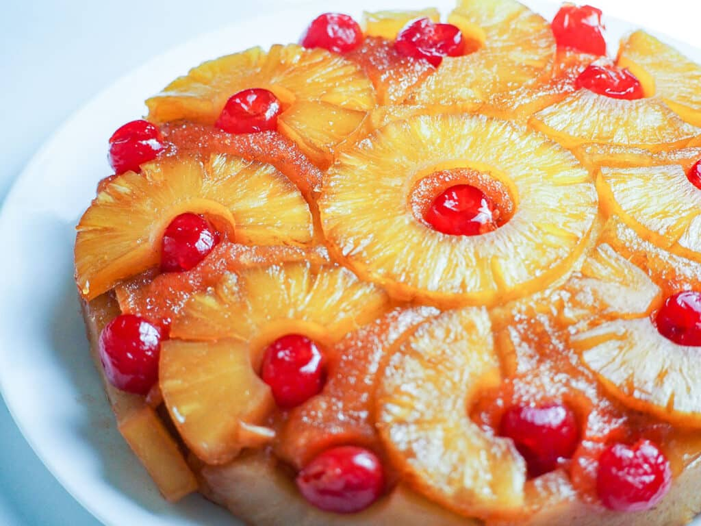 pineapple upside down cake on white plate on white background