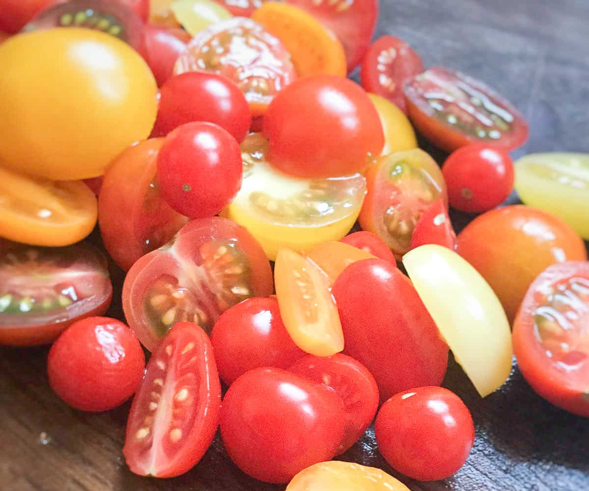variety of small tomatoes on cutting board whole and sliced