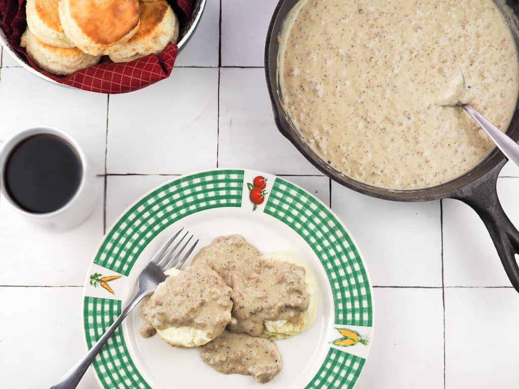 biscuits and gravy on a plate surrounded by coffee gravy in pan and biscuits in bowl