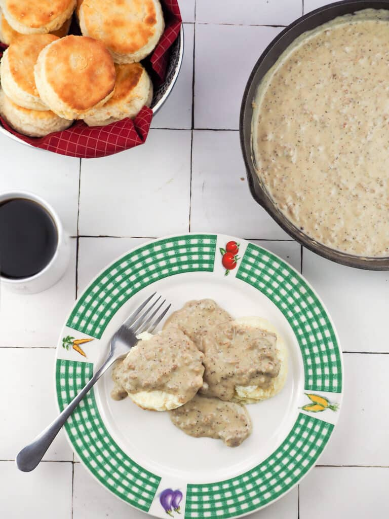 biscuits and gravy on plate topped with sausage gravy with bowl of biscuits in top left and pan of gravy in top right