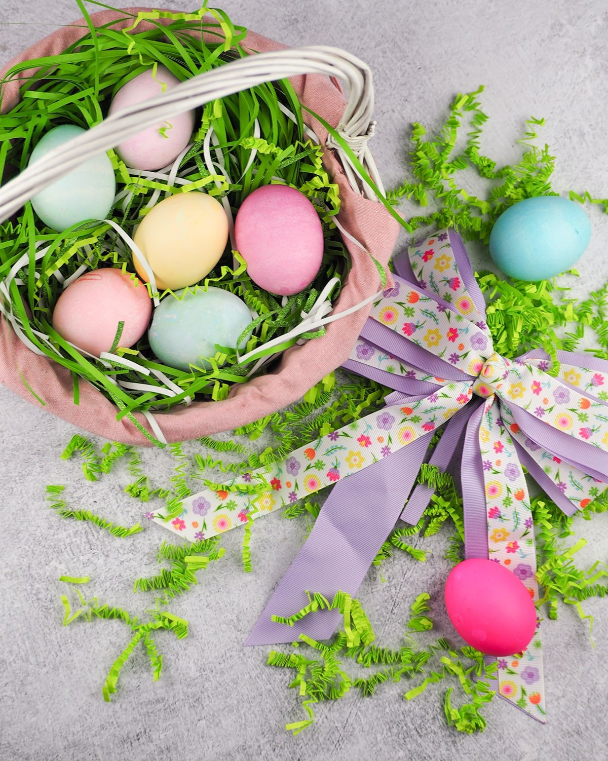 overhead view of easter eggs in basket with artificial grass more eggs and cloth ribbon offset to right