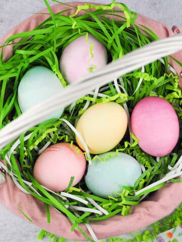 overhead of colored eggs in basket