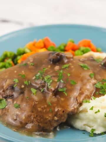 smothered cubed steak on blue plate with mashed potatoes and vegetables