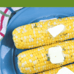 corn on the cob on blue plate with butter pats on top