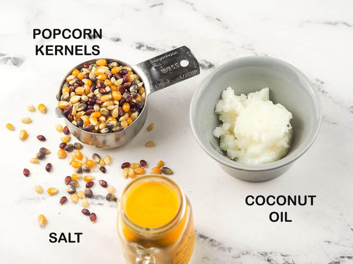 popcorn, coconut oil, and popcorn salt on marble table