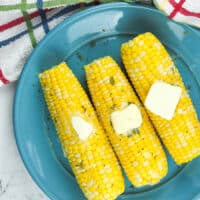 three ears of cooked corn on blue plate