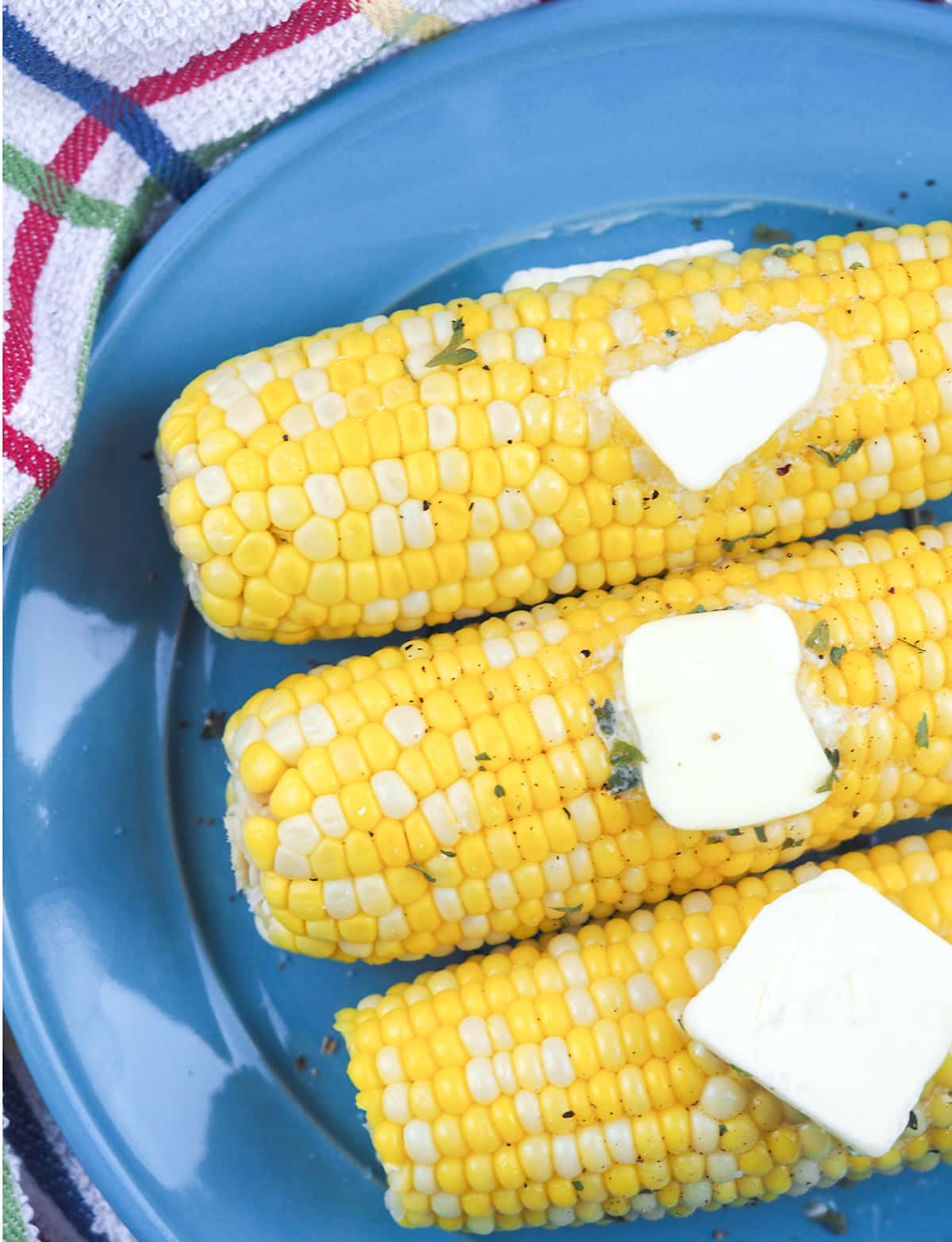 close  up view of three ears of corn on the cob on blue plate with butter pats and sprinkled parsley