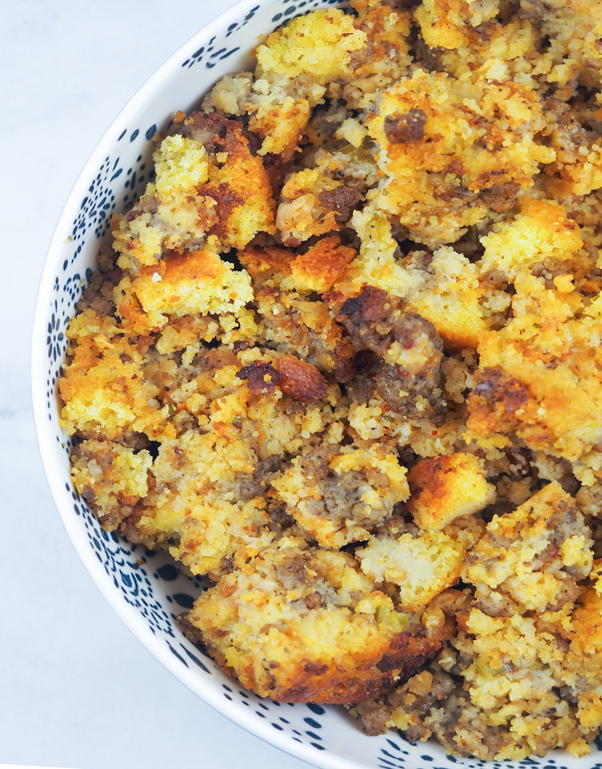 overhead close view of cornbread stuffing in white bowl with blue stamped pattern