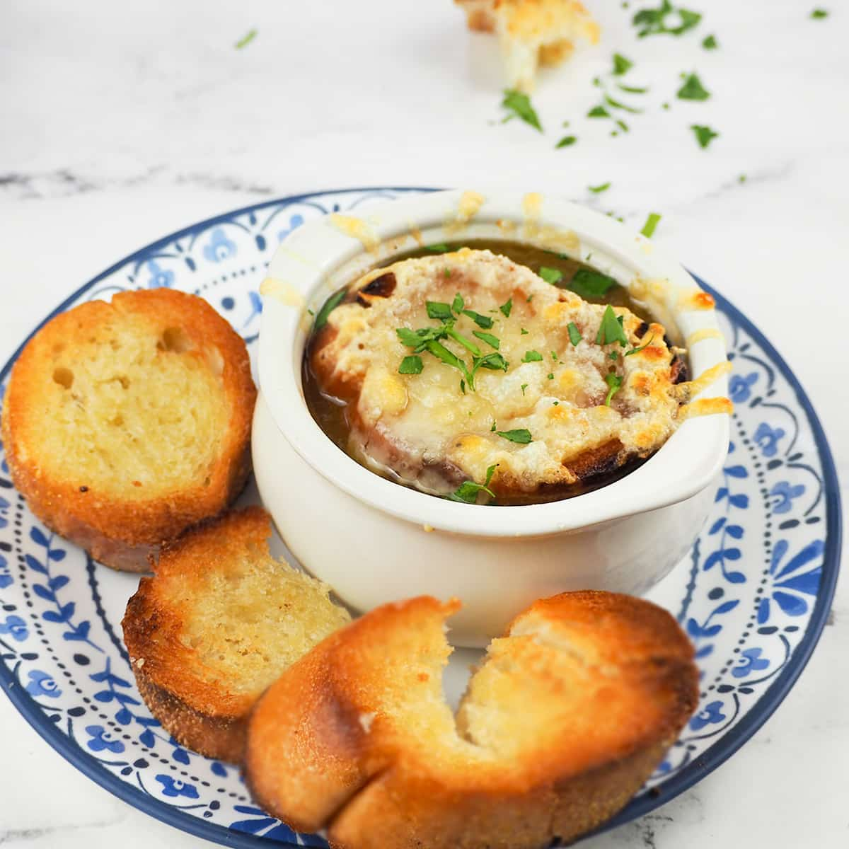 soup topped with cheese on plate with toasted bread