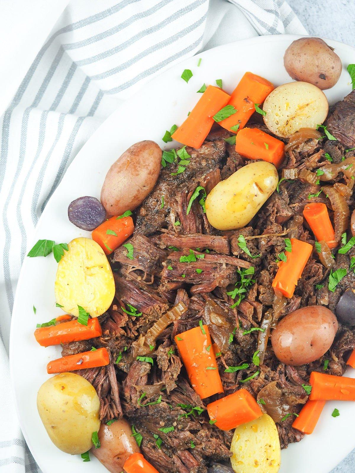 shredded pot roast on platter with vegetables
