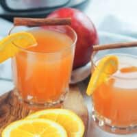 glasses of apple cider garnished with orange slice and cinnamon sticks