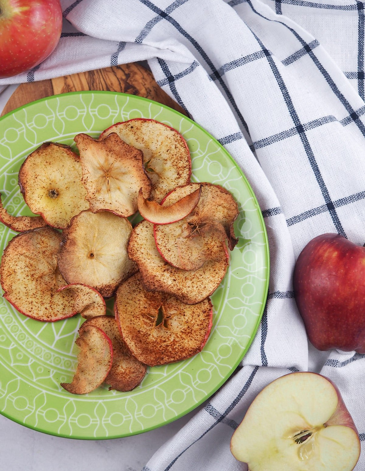 apple chips on green plate next to red apples