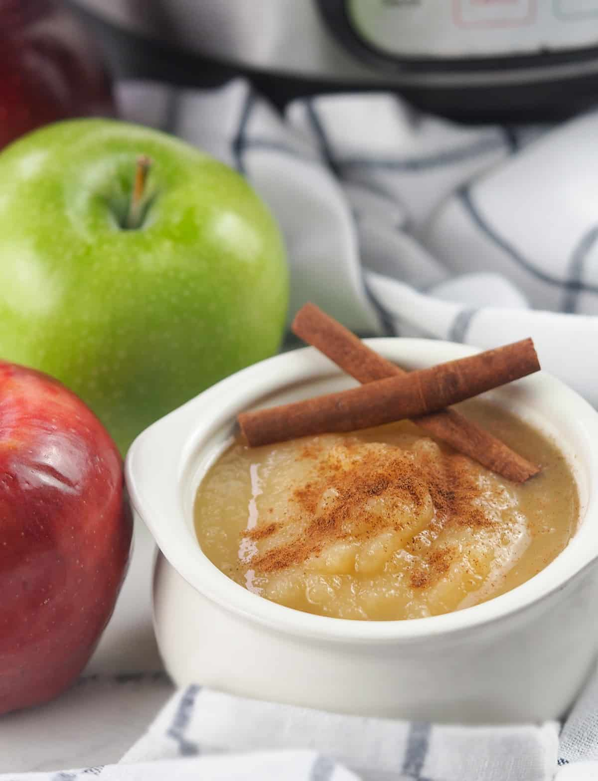 applesauce with cinnamon in white crock bowl with fresh apples