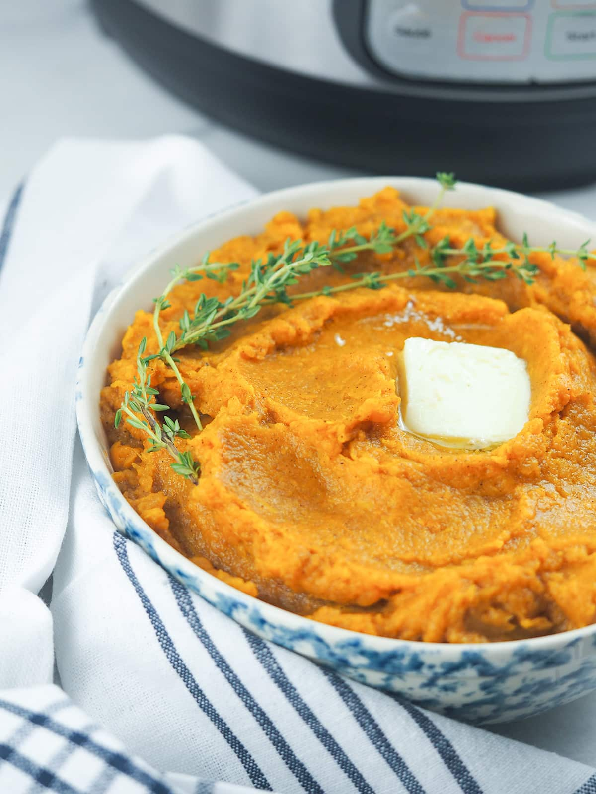 mashed sweet potatoes in blue and white bowl in front of instant pot