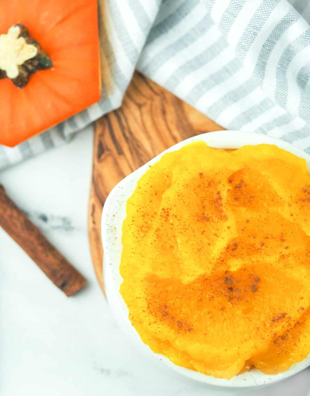 pumpkin puree in white bowl next to pumpkin stem
